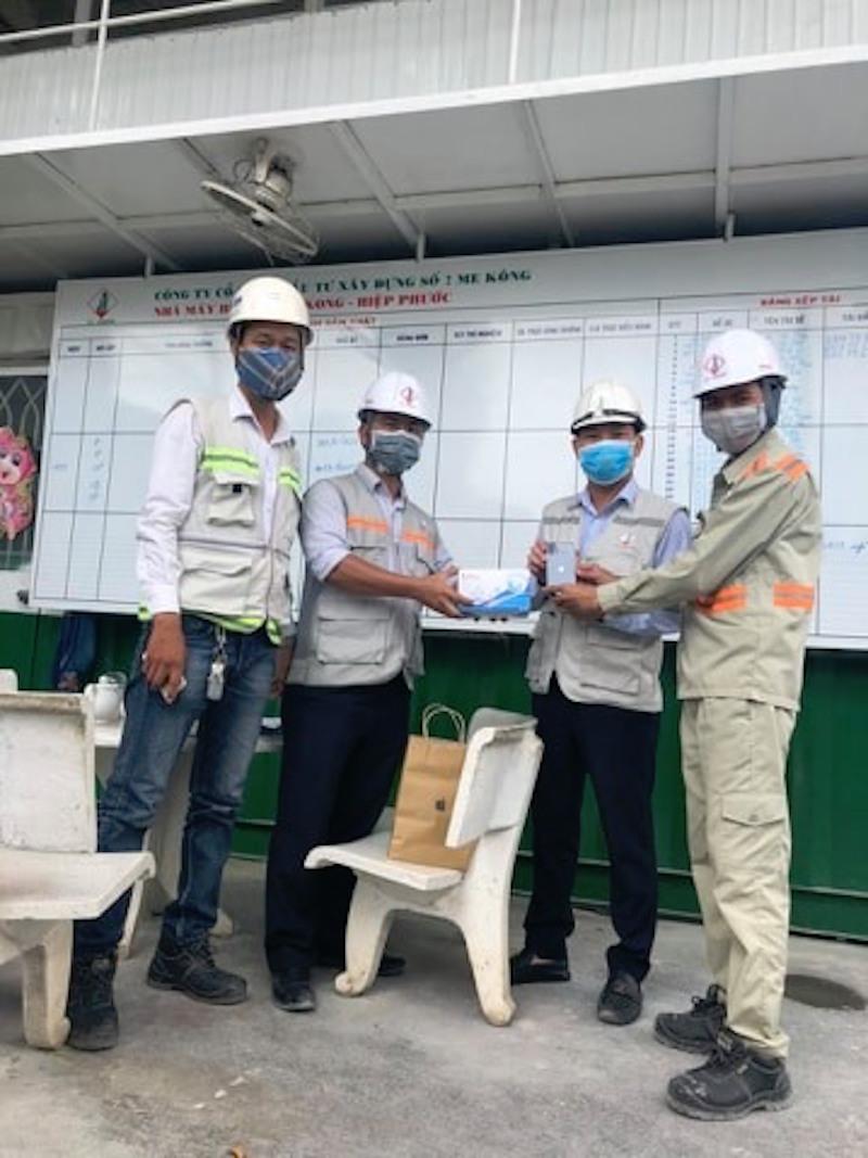 Anh Trần Quốc Lập vừa trao tặng những chiếc điện thoại Iphone XI và khẩu trang cho nhân viên của mình
