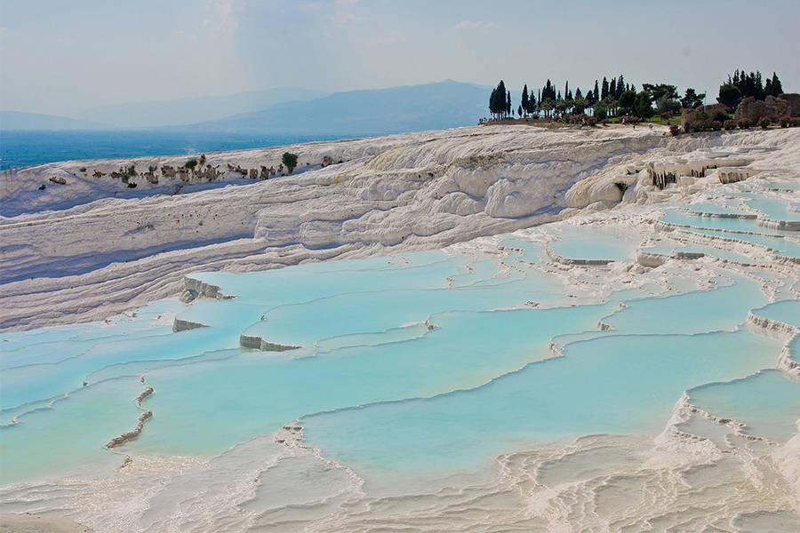Nhìn từ xa Pamukkale trắng xóa cứ như một ngọn núi tuyết, nước suối đọng giữa những lớp đá vôi thành các hồ nước nhỏ xanh ngắt.