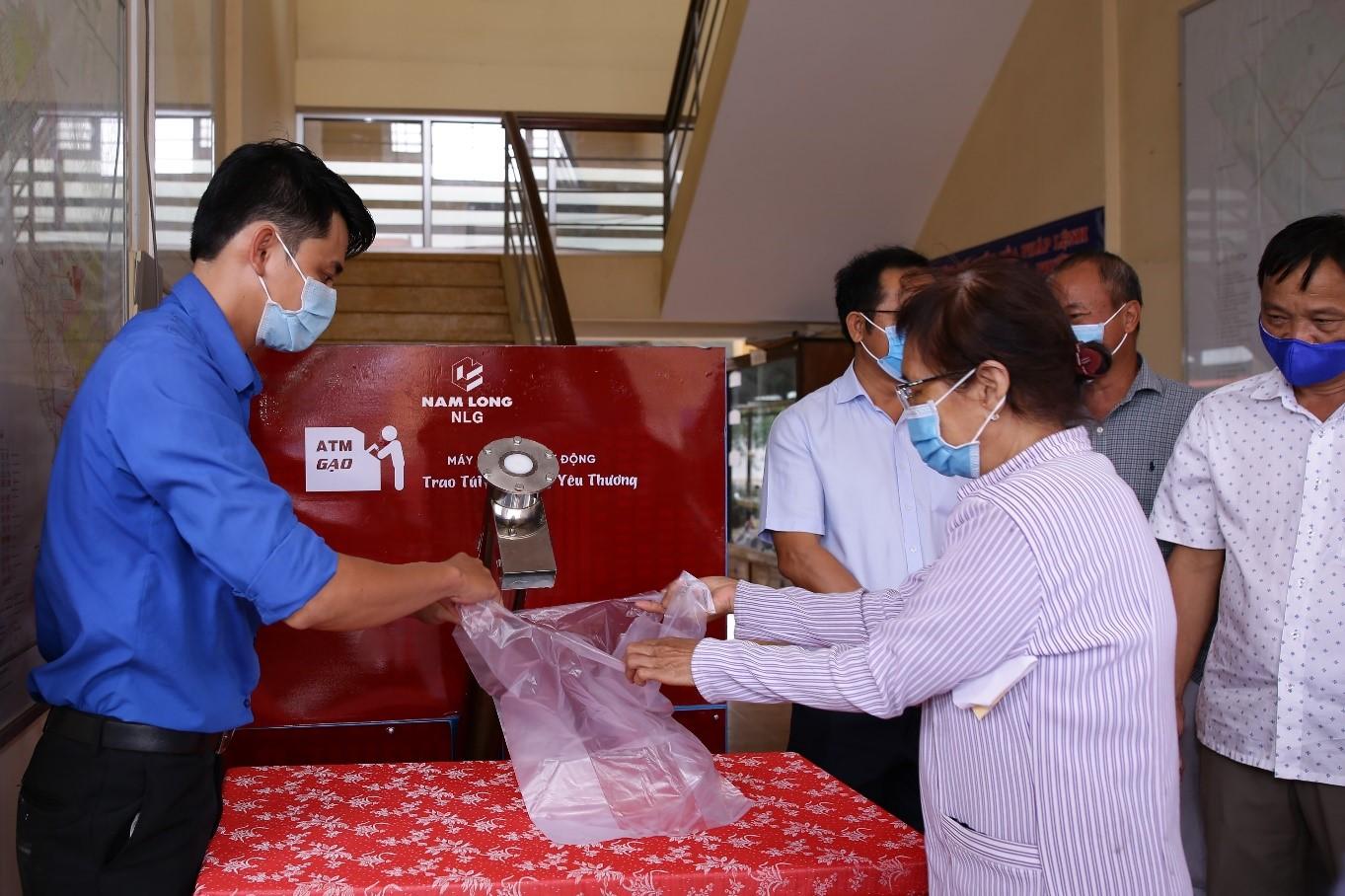 Cán bộ địa phương hỗ trợ người dân nhận gạo từ máy.
