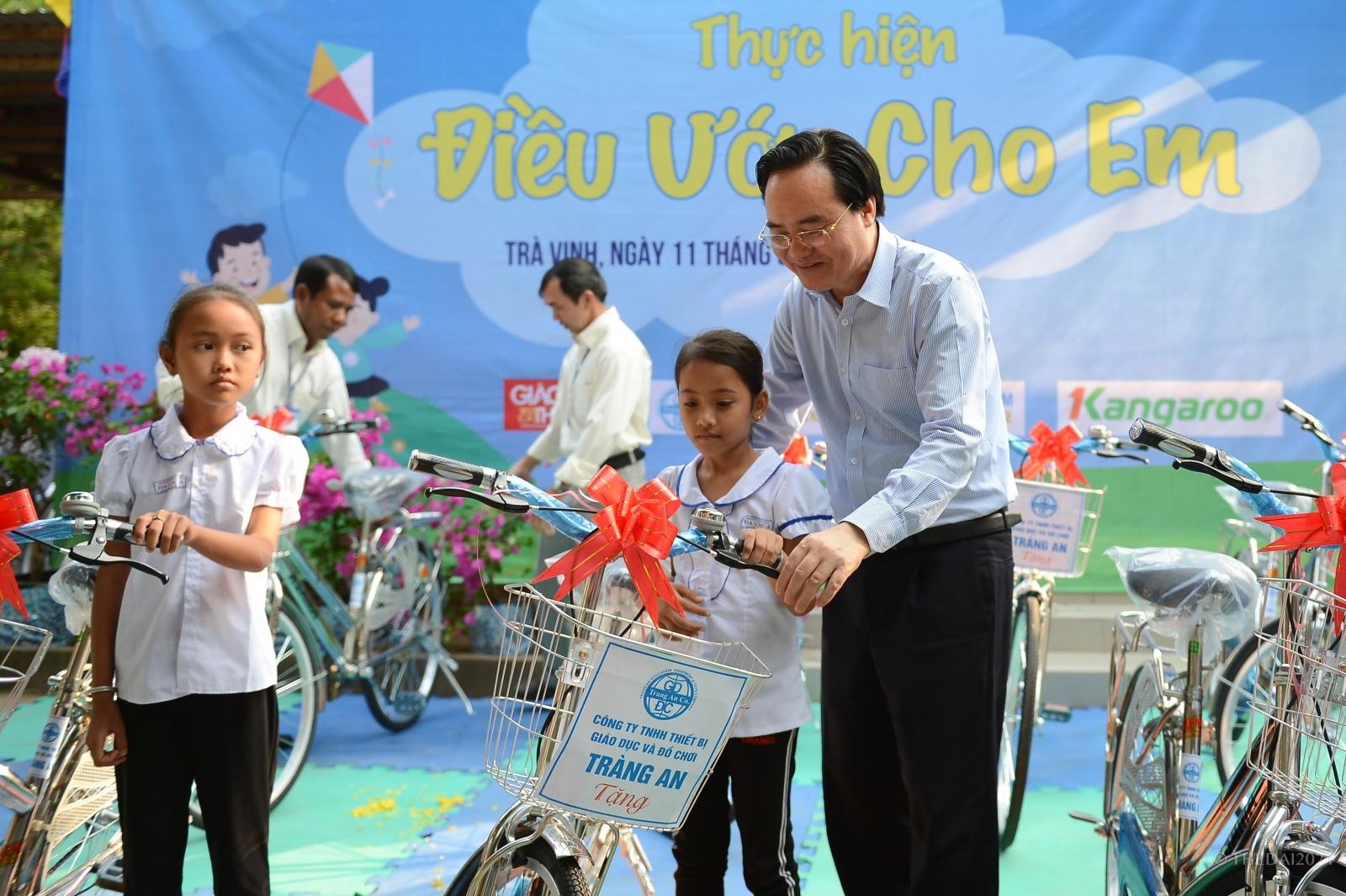 Bộ trưởng Bộ GD&ĐT Phùng Xuân Nhạ trao xe đạp cho HS nghèo Trường TH Đa Lộc A, huyện Châu Thành (Trà Vinh). Ảnh: Thế Đại.